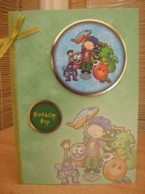 """This fun card measures A5 in size and comes with a white envelope and protected in a cello bag. The topper, features a boy with his toys, it has gold foiled edging and has been raised to give dimension. The sentiment reads """"Birthday Boy"""". A gold ribbon and bow has been added to decorate. The inside has been left blank for your own personal message. http://www.makesellbuy.com/products/view/136299400889/handmade-birthday-card-boys-and-toys"""