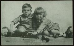 Vintage advertising postcard of children with toy train - advertising Kin-der Kids Play Suits.