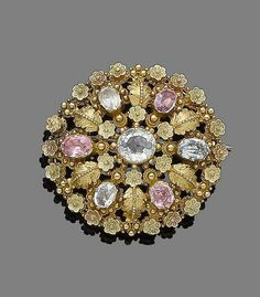 A gem-set brooch The openwork oval plaque, centrally-set with an oval-cut aquamarine, within a surround of floral and foliate design, decorated with similarly-cut foiled pink and blue topaz and aquamarines, with beaded detail, length 4.3cm