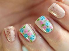 unhas decoradas com flores na cor azul e rosa com fundo nude