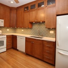 Light wood floors, medium wood cabinets, muted green backsplash