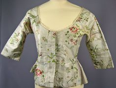 Bodice, c. 1770-1780. Pale green silk brocade embroidered with floral and leaf patterns, lace trimming.