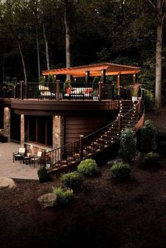 A lighted staircase leads to a spacious deck with a large wood pergola. A metal railing surrounds the second-story deck creating an elegant escape nestled in the woods. Maybe put this on top of a natural waterfall for a backyard pool? Rooftop Patio, Backyard Patio, Backyard Seating, Rustic Backyard, Backyard Canopy, House Canopy, Deck Seating, Pvc Canopy, Canopy Crib