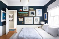Orlando Soria's guest bedroom not only features an immaculately-styled gallery wall but an enthralling shade of blue that elevates the dreamy scene.