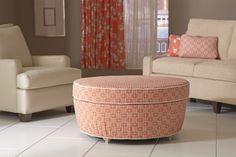 The attractive round, attached-pillow-top ottoman sports a unique tapered base. I Rowley Company