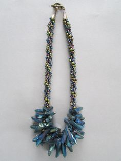 NoGlitzNoGlory. This stunning necklace has been made with peacock colored Quartz stick crystals, freshwater pearls, Chinese crystal and Miyuki beads.