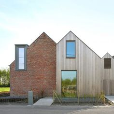 Atelier Tom Vanhee adds pair of gabled extensions to brick farmhouse in Belgium