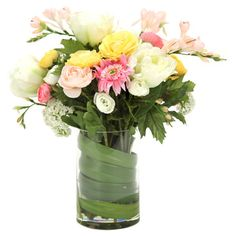 Create a lush tablescape or charming vignette with this blooming arrangement, featuring faux tulips, ranunculus, and snowballs in a cylindrical glass vase.