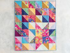 "Who knew it was this easy to make 10"" squares look so stunning? Star Light Star Bright uses 10"" squares to transform simple half-square triangles into a fun and eye-catching design. This project, featuring the Madison Park collection from Lily & Loom, also leaves plenty of room for some creative machine quilting."