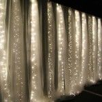 tinted tulle and lights from ceiling to floor behind a bed for a bedroom....beautiful backdrop