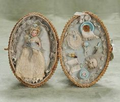 "19th century doll in basket 3.5"" (9 cm.) doll. 9"" basket. An egg-shaped basket with interwoven blue silk ribbons hinges open to reveal a well-fitted interior of blue silk and lace edging, containing an all-bisque doll with painted features, blonde mohair wig, peg-jointed limbs, painted shoes and socks, wearing beautiful long original lace Christening gown and bonnet, along with an assortment of original accessories including rattles, pacifier, puff, brush, bib, and more. Excellent condition…"