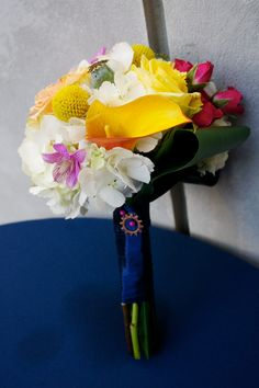 Multicolored bouquet with hydrangea, calla lilies, and hypericum berries with ti leaf. Wrapped in navy. Photo by Justin Wright, Flowers by Brocade Designs