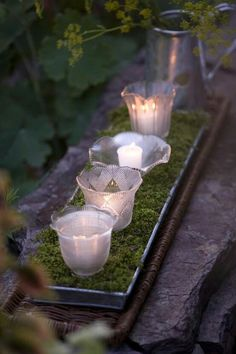 Votives on moss in a metal plant tray. Use mixed glass containers of the same size to hold the candles - jars, glasses, . These are globes off of light fixtures.