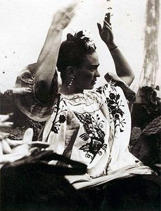 Black and white photo of Frida Kahlo gesticulating to someone outside the camera view.