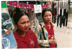 """We begin the book """"Half the Sky"""" with the story of Srey Rath, the Cambodian woman on the left. She was trafficked to Malaysia, brutally mistreated and finally escaped by climbing on a rickety ladder from her building to the next. Upon her return to Cambodia, she started this little business selling trinkets, and it is a great success. She turns out to be a terrific businesswoman. Sadly, her cousin, Srey Hoi, on the right, has disappeared and perhaps has been trafficked."""