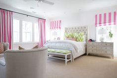 Fabulous girl's room features tufted bed dressed in crisp white bedding and white and green chevron shams flanked by French dressers as nightstands topped with mercury glass table lamps situated under windows covered in white and pink striped roman shades as well as a green chevron bench placed at the foot of the bed. A small bedroom sitting area boasts linen chairs with silver nailhead trim placed in front of window accented with white and pink candy stripe curtains.