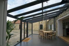 Modern lean-to conservatory with large glazed panels, metal frames & no shading.