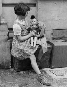 12th June 1940: A young Italian girl waits outside the Italian embassy in London with her doll, while her parents make arrangements to return home after Italy's entry in to World War II. | vintage children style | 1940s girl dress + haircut | 40s life