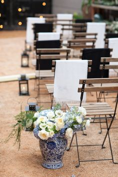 Outdoor wintertime wedding ceremony, blue china vases, cream and blue floral arrangements, lanterns down the aisle, shawls on chairs // Julie Mikos | Photographer