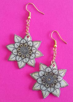 Shrink plastic earrings. Black and gold detail on white background.