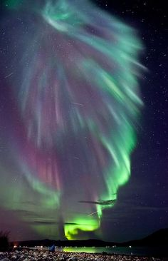 Aurora Over Norway - Besides this spectacular multicolored aurora, the photographer caught three satellite streaks, one airplane streak, and a friend trying to capture the same sight. Although auroras might first appear to be moonlit clouds, they only add light to the sky and do not block background stars from view. Called northern lights in the northern hemisphere, auroras are caused by collisions between charged particles from the magnetosphere and air molecules high in the Earth's atmosph...