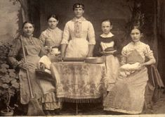 Here is a rare look at a group of house servants, circa 1880-90. Each gal is holding something to do with her occupation. On the far left is a cleaning maid with her broom and dustpan. Next is a young girl holding what looks like a cup and saucer. In the center is a lovely cook with her rolling pin and bakery pans. Next is a very young girl holding either a pudding or small cake. Finally, we see a girl holding a rather mysterious object (a shoe? a sugarloaf?). Fascinating!