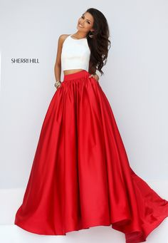 The Sherri Hill 50134 is a two-toned two-piece prom dress, designed with a contemporary ball gown silhouette. Arm-to-waist darts taper the crop top, held with a thin halter strap that wraps over the semi-open back. In-seam pockets adorn the fully gathered skirt, which begins with a natural waistband, and flows with a tulle lining towards the court train.