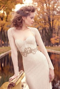 Ivory/Gold chantilly lace trumpet bridal gown, corseted lace bodice with golden jewel filigree at natural waist, sweetheart neckline, fitted lace sleeves, keyhole back, chapel train. Available in Ivory/Silver. Style LZ3512 by JLM Couture, Inc.