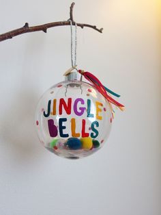 This is a big and beautiful 8cm diameter Round Bauble.   Hand painted name in a fun colourful font, with polka dots.  Can also be painted with Jingle Bells (as pictured) a personal message, for a new baby, or just your name.   Filled with a pom pom, bead and sequin mix, and finished with a satin bow or Ribbon Tassel.   Presented in a Giftbox for a one of a kind Christmas Gift.   This is a made to order item and I can tailor to most requests. Check out my store for other designs, and pe…