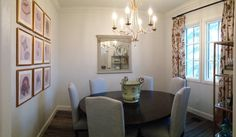 Formal dining. Art wall, round table, gold chandelier, gold frames, light blue chairs, white walls.