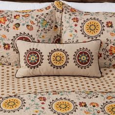 Fiery suzani sun discs and floral crests adorn this retro style decorative pillow. Crafted of cotton, this charming embroidered pillow reverses to an all-over foulard print and coordinates with a variety of home decor styles.