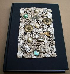 I decorated the front of this blank journal with a handmade polymer clay plaque. I wove strips of beige, white and ivory clay together and added glass gems, jewelry bits, metal ornaments and an old key.oh, and the buckle from a watch band LOL! Polymer Clay Projects, Polymer Clay Art, Handmade Polymer Clay, Resin Art, Polymer Journal, Crea Fimo, Journal Covers, Book Covers, Blank Journal