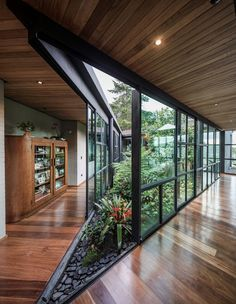 A central open-air garden filled with plants connects the wings of this modern house, with sliding glass walls opening the garden to the interior. # architecture This Triangular Shaped House Makes Room For An Interior Garden Interior Garden, Home Interior Design, Interior Architecture, Garden Architecture, Residential Architecture, Interior Modern, Modern Architecture House, Concept Architecture, Drawing Architecture