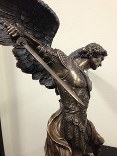 The kind of hybrid arm/wing is interesting here. St. Michael the Archangel standing on a demon statue