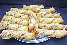 Blätterteig - Nussstangerl 《2 Pkt. Blätterteig》 40 g Butter《 200 g Nüsse》 1 Ei(er)《 100 g Zucker《 1 Pck. Vanillezucker《 Puderzucker, zum Bestäuben