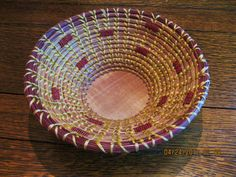 Coiled pine needle basket with maroon top coil and maroon seed beads woven into the wall