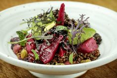 Roasted beets and purple quinoa in a rustic pottery bowl, topped with herbs, crisply roasted pistachios, chunks of buttery Reed avocado and ...