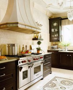 Kitchen - gorgeous - glossy lava-stone countertops - walnut cabinetry  - plaster-relief medallions and deep crown moldings that add detail to the ceiling - an ornate tile mosaic 'rug' | Robert Schwartz and Karen Williams via Traditional Home