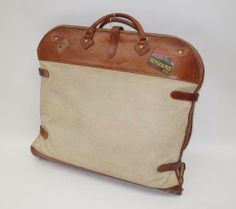A Hermes suit-bag, circa 1940, beige canvas with brown leather handles, trim and straps with brass buckles, with zip opening to interior complete with single wooden coat-hanger, some travel labels to exterior trim, measuring 129 x 64cm fully open.