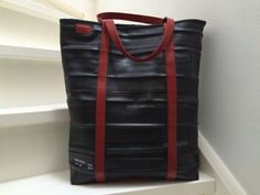 Big shopper, made of innertubes and red leather handles. Lining sail of the sailboat