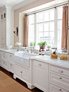 Furniture style cabinetry, farmhouse sink above cabinets, marble.