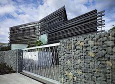 clôture moderne en pierre naturelle et verre transparent entourant le jardin…