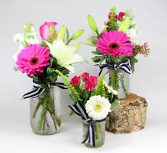 mason jar trio: various mason jars with hot pink and white gerbera daisies, roses, lilies, stockflower and spray roses accented with a knotted navy and white grosgrain ribbon.