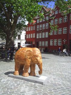"""Woodphant"" by Ekapong Ruen-oon at the Elephant Parade in Copenhagen, Denmark, 2011 - photo from danculture.dk;  one of 102 decorated elephants around Copenhagen in 2011;  the red house in the background, ""Ildebrandshusene"" was built in 1735."