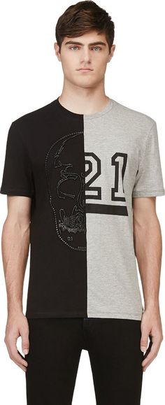 Short sleeve t-shirt in black and heather grey. Ribbed crewneck collar. Contrasting effects at front with accent seam running through center. Graphic print at one side of front in black. Signature skull feature at other half in looped black leather. Black stitching.