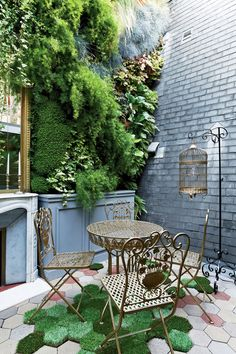 Gorgeous Floral Wrought iron patio table and chairs with Vertical Garden wall - Love the bird cage and grass pavers