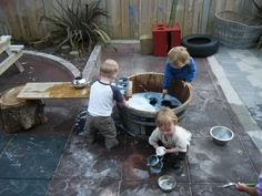Use a wooden plank as a table top during water play. I love the washing bin and tree stump!