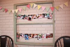 First birthday party photo collage. One photo for each month hanging on wire from an old window pane. All of these pics had the birthday girl with her fav. black lab doll, to go with the theme of the party.