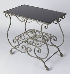 French Wrought Iron Rolling Serving Cart <p>A forged iron Serving Table from Lyon with a smoked black glass top and a bottom shelf. The ironwork with scrolls and twists is very graceful. The Table rolls on casters.</p>