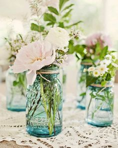 Flower arrangements in blue mason jars - 2 larger jars like in picture, 2 smaller jars like in picture. Muted pink tones like peonies and pretty white flowers and greenery.